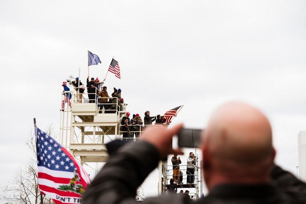 متظاهر مؤيد لترامب يلتقط صورة لمتظاهرين آخرين تسلقوا منصة إعلامية بعد أن اخترقوا الحواجز في مبنى الكابيتول - 6 يناير 2021 (أ.ف.ب)