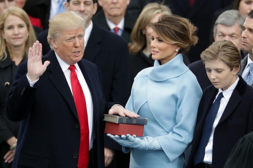 ترامب يؤدي اليمين الدستوريّة بينما تحمل زوجته ميلانيا الانجيل (أ.ف.ب)