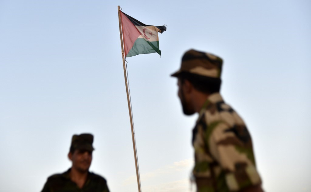 جنود من جبهة البوليساريو أمام علم صحراوي يرفرف في مخيم