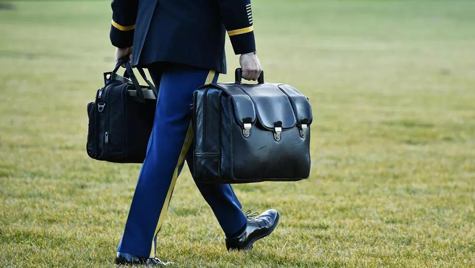 معاون عسكري لدونالد ترامب يحمل الحقيبة النووية التي تحوي شيفرات وإجراءات توجيه ضربة نووية (ا ف ب)