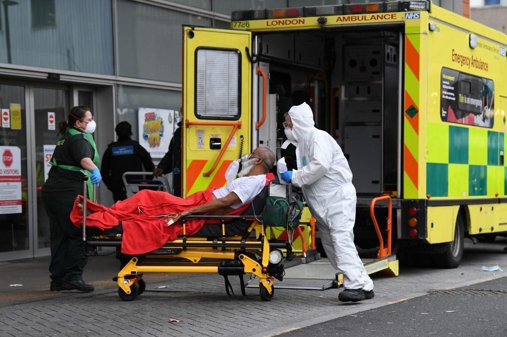 مسعفون ينقلون مصاباً بكورنا إلى المستشفى (أ ف ب)
