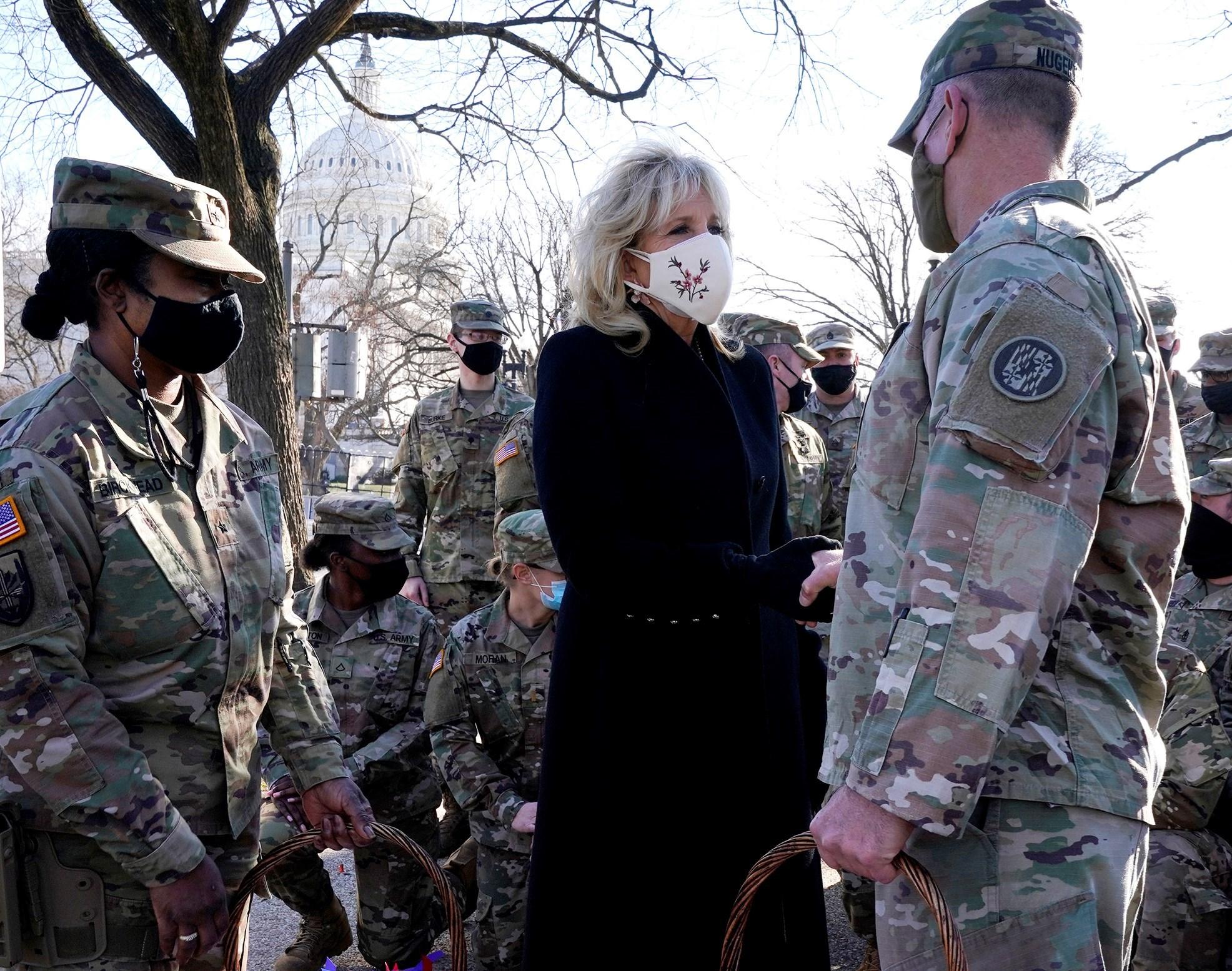 جيل بايدن تحيي أعضاء الحرس الوطني خارج مبنى الكابيتول في واشنطن (أ ف ب).