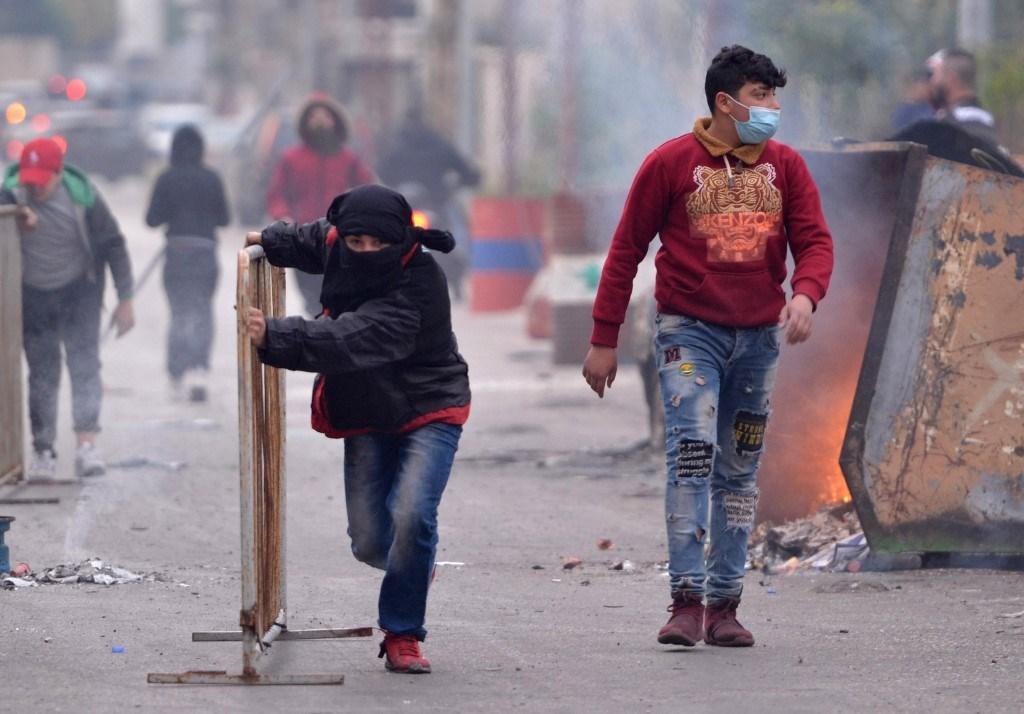 متظاهر يحمل حاجز معدني خلال المظاهرات المستمرة في مدينة طرابلس شمال لبنان / 27 يناير 2021 (أ ف ب).