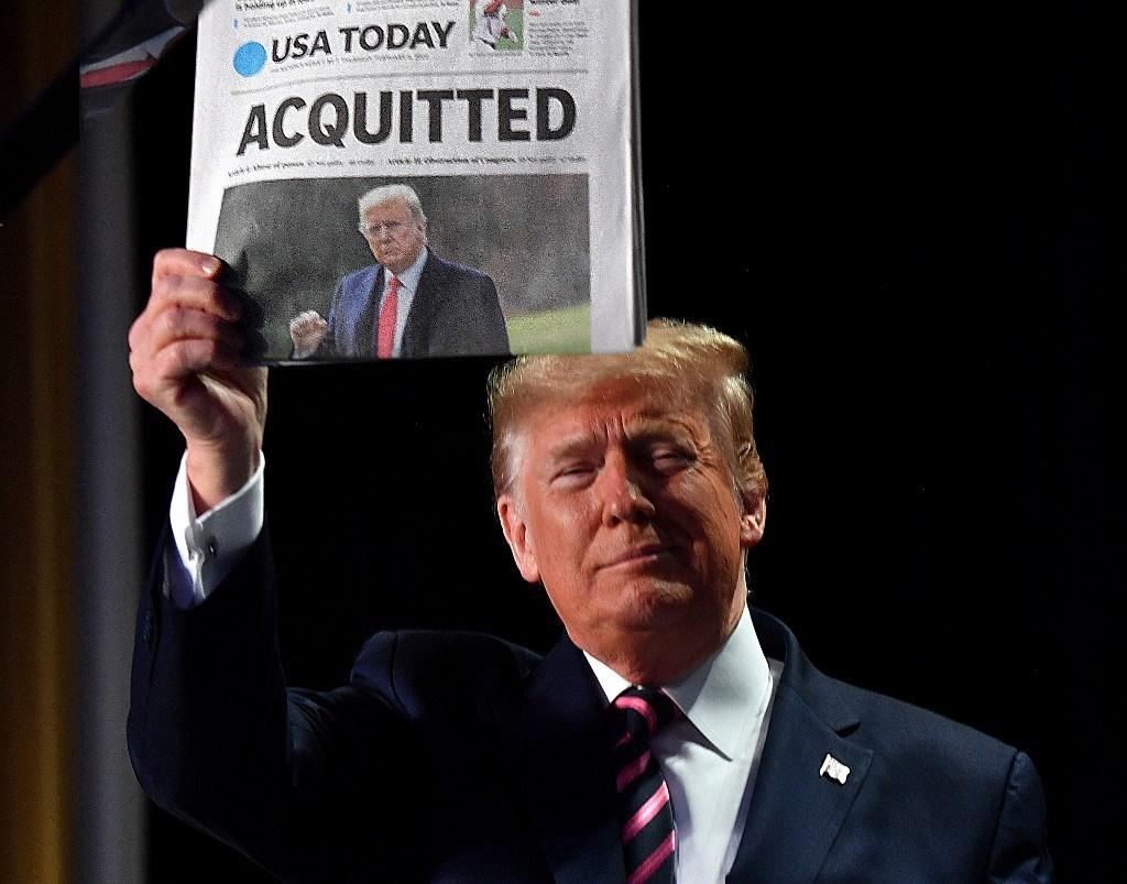 ترامب يحمل صحيفة تحمل عنوان