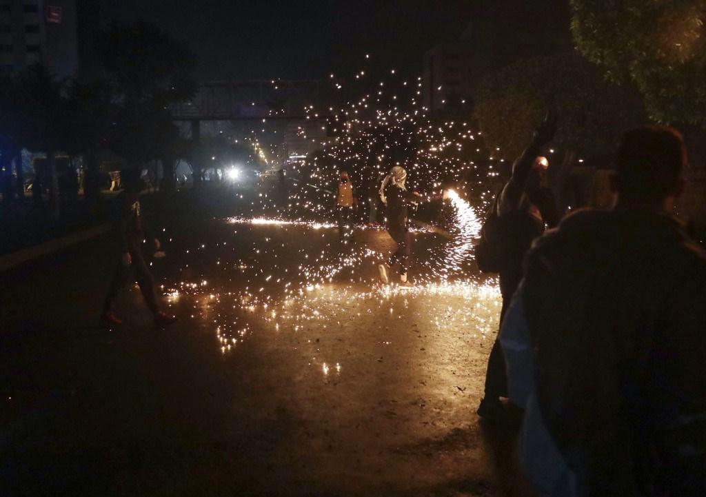 متظاهر لبناني يرمي عبوة حارقة وسط اشتباكات مع قوى الأمن أمام سراي طرابلس - 28 يناير 2021 (أ.ف.ب)