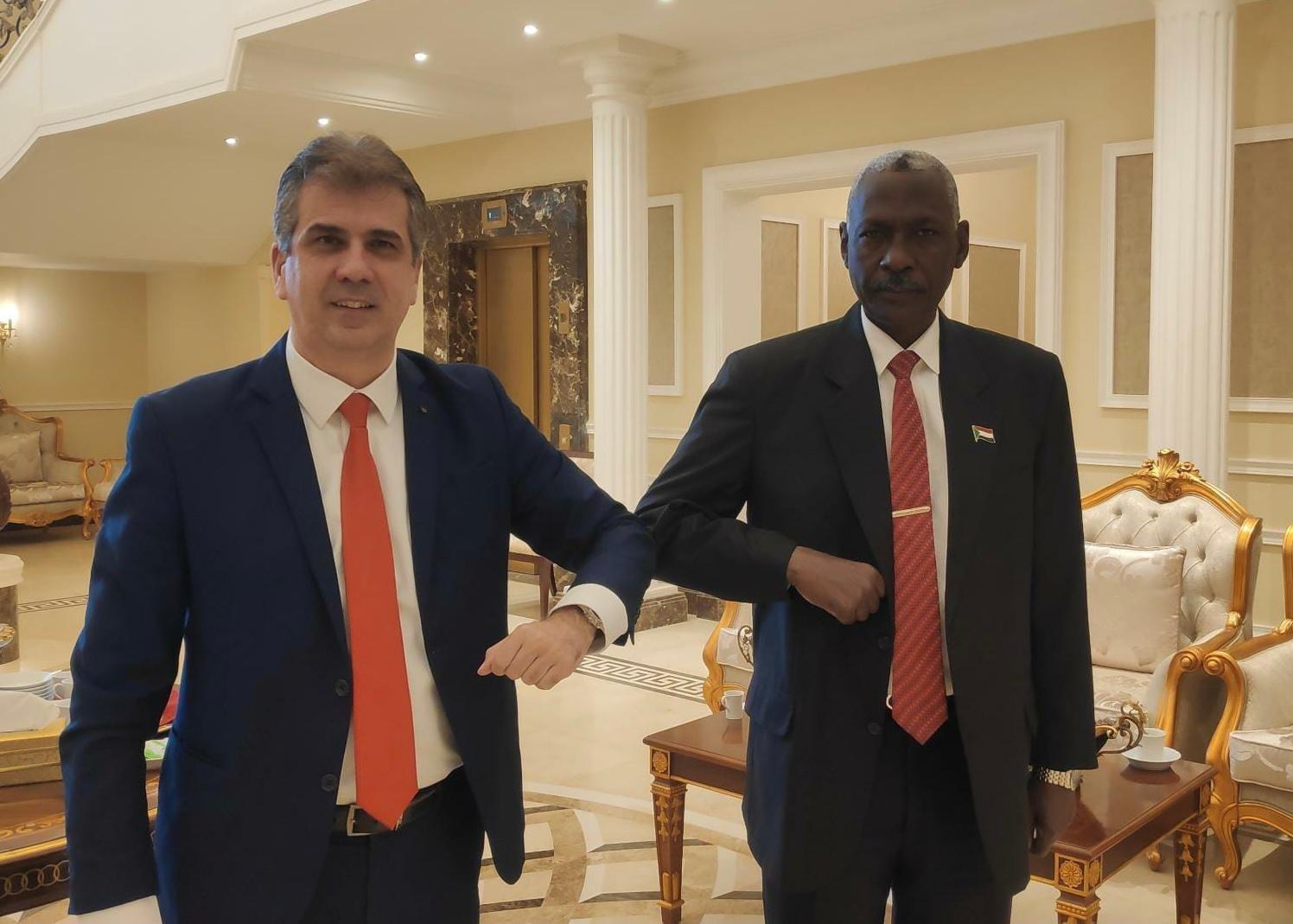 وزير المخابرات الإسرائيلي إيلي كوهين يتبادل وثيقة مع وزير الدفاع السوداني ياسين إبراهيم خلال اجتماعهما في العاصمة السودانية الخرطوم