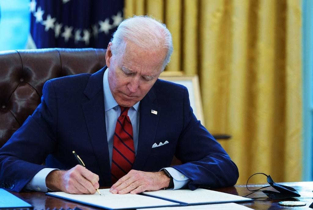 بايدن يوقع أوامر تنفيذية في المكتب البيضاوي للبيت الأبيض في واشنطن - 28 يناير 2021 (أ ف ب).