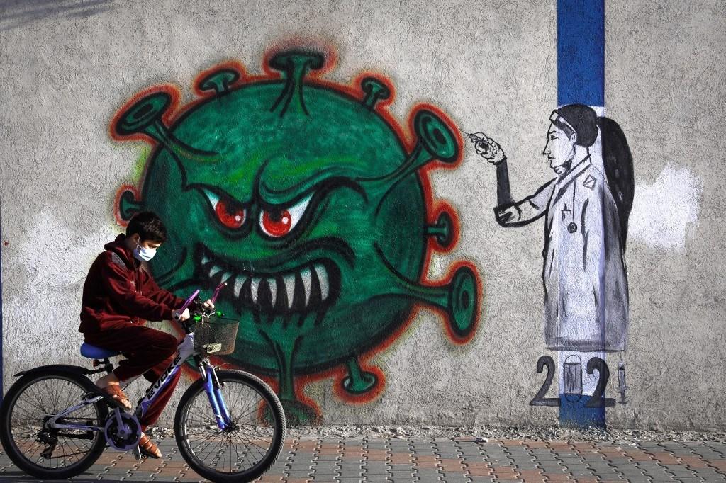 شاب فلسطيني على دراجته أمام لوحة جدارية لممرضة تحقن لقاحاً لفيروس كورونا في غزة - 31 ديسمبر 2020 (أ.ف.ب)