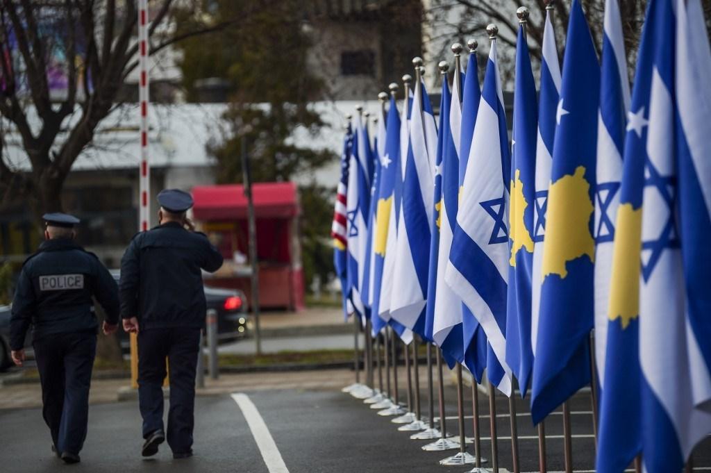 ضباط شرطة كوسوفو يمشون أمام علمي كوسوفو و