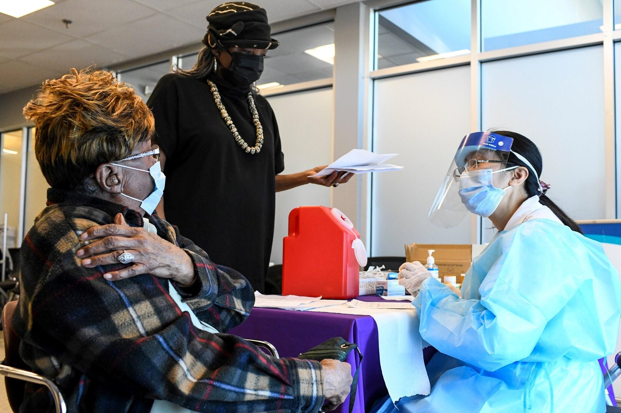 مواطنة أميركية وابنتها تتلقان اللقاح في واشنطن - الصورة لنيويورك تايمز.