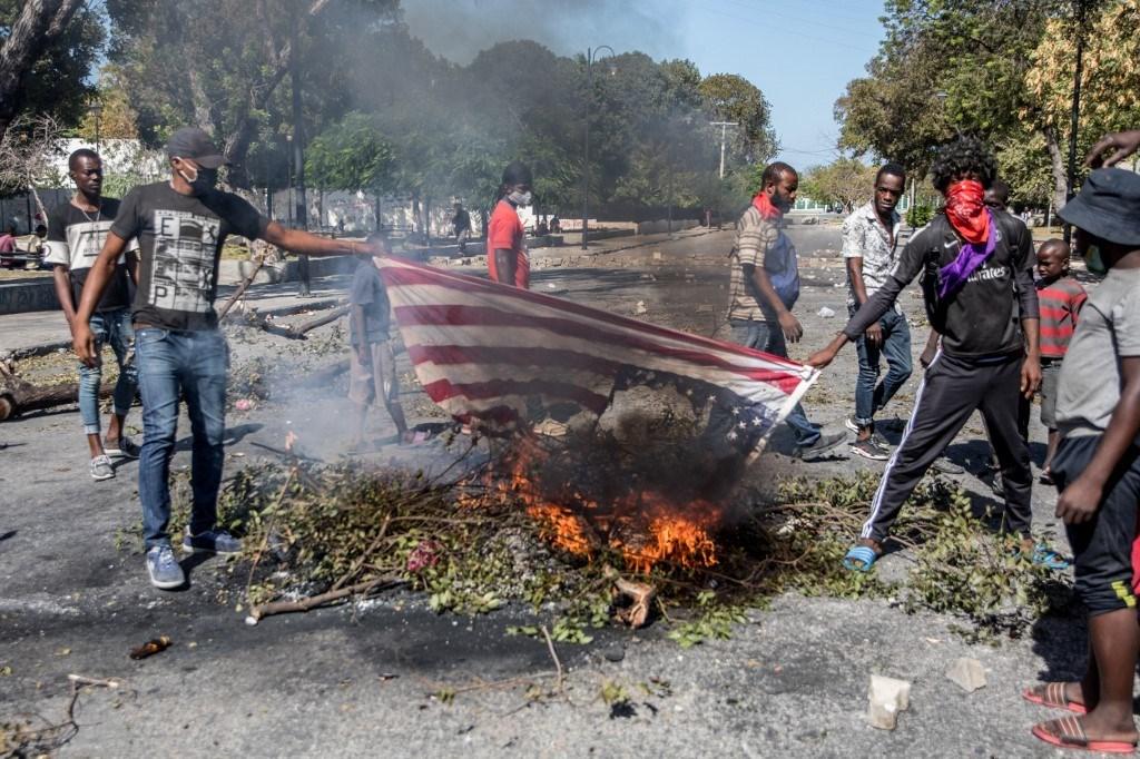متظاهرون يحرقون العلم الأميركي خلال احتجاج للمطالبة باستقالة الرئيس في هايتي 2021 (أ ف ب).