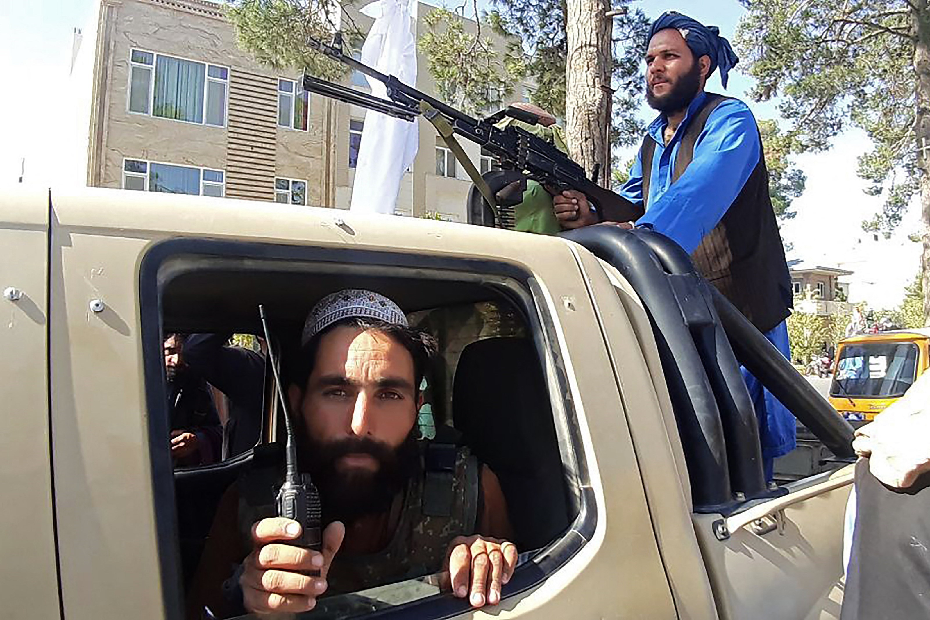 Taliban fighters in a vehicle along the roadside in Herat