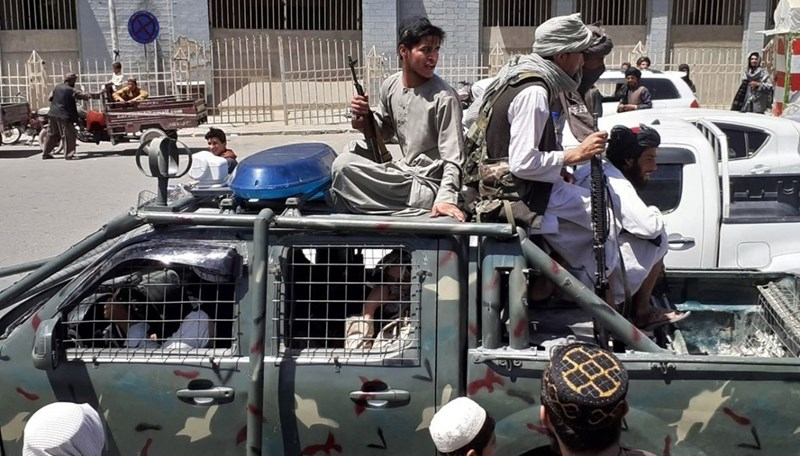 Taliban fighters ride in an Afghan National Directorate of Security car in Kandahar.