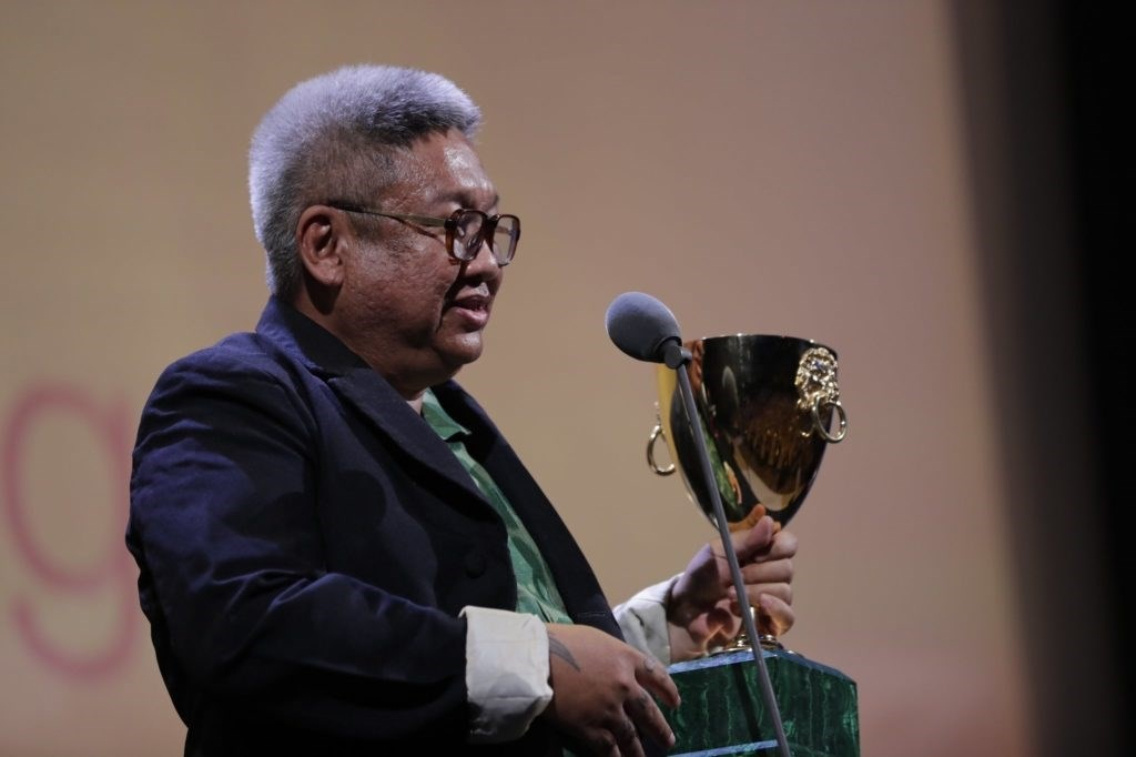 Director Erik Matti receives the award in the name of.... due to the latter's absence