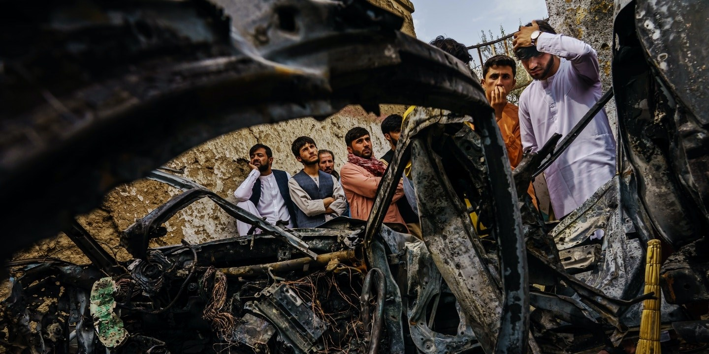 Relatives of the Ahmadi family gather around the incinerated husk of a vehicle targeted and hit by a US drone strike that left 10 dead, Kabul, Aug 30, 2021 | Getty